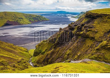 Canyon Pakgil in Iceland. Basalt hills covered with green grass. Streams from melting glaciers flowing down the canyon