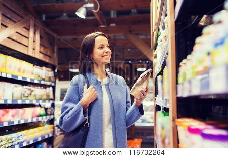 happy woman choosing and buying food in market
