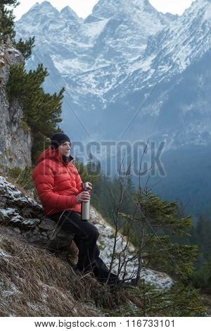 Resting mountain hiker with hot drink cup in hand at snowy winter mountains background