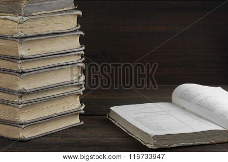 Single Open Book And Old Shabby Books In Stack