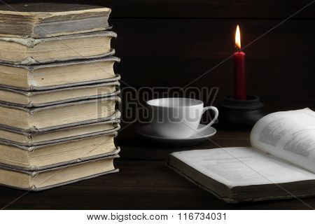 Old Shabby Books, White Cup, Lighted Candle On Wood  Background