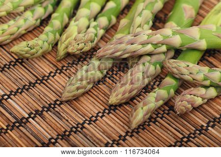 Ripe Green Asparagus On Wooden Mat