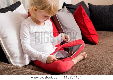 Little girl sitting on couch with tablet in her lap