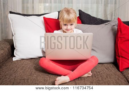 Little girl watching something in computer