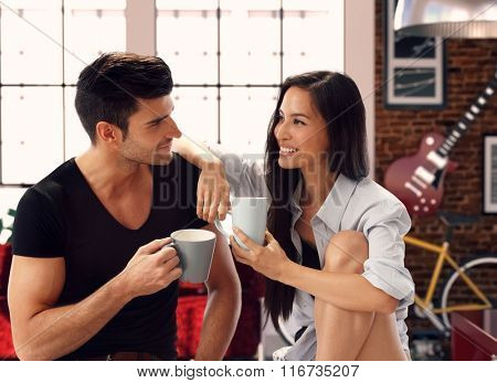 Happy young loving couple sitting at home, drinking tea, smiling.