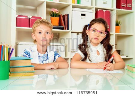 Children sit at the table with books. Educational concept.