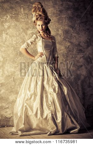 Fashion portrait of a beautiful woman in a luxurious medieval dress and high hairdo in vintage style. Baroque and Renaissance style. Historical dress, hairstyles history. Sepia.