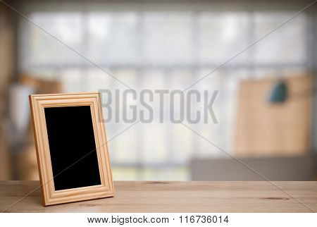 photo frame on the wooden table in old room with big windows