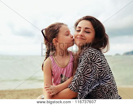 Cute Kid Girl Kissing Her Happy Enjoying Mother With Closed Eyes And Natural Emotion On Sea Backgrou
