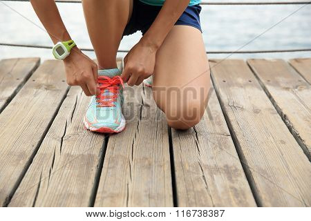 sports woman runner tying shoelace on wooden boardwalk seaside