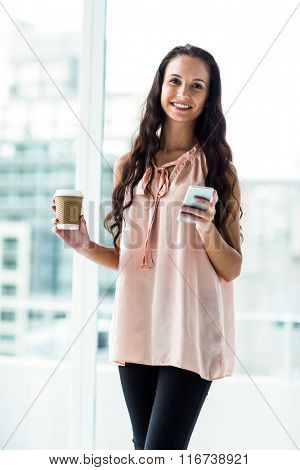 Smiling woman using smartphone holding disposable cup against window