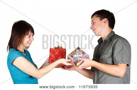Young Brunette Girl And Man Present Gifts To Each Other And Smiling