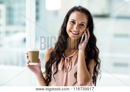 Smiling woman on phone call holding disposable cup next to window