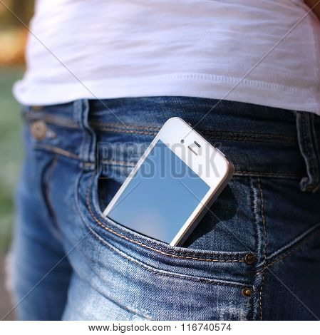 Close-up Portrait Of Black Smartphone In Back Pocket Of Girl's Jeans