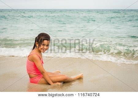 Little Girl Playing With A Starfish On The Beach