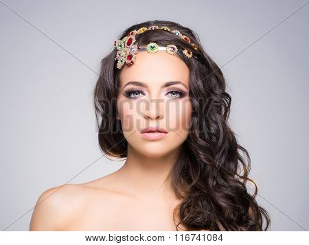 Attractive, curly brunette with flower alike golden headband with different gems over gray background.