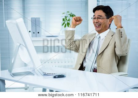 Smiling businessman with arms raised