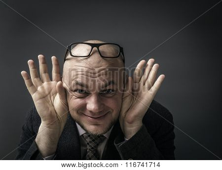 Bald businessman with hand behind ear listening closely against gray background