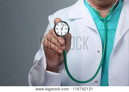 Male doctor holding stethoscope with clock