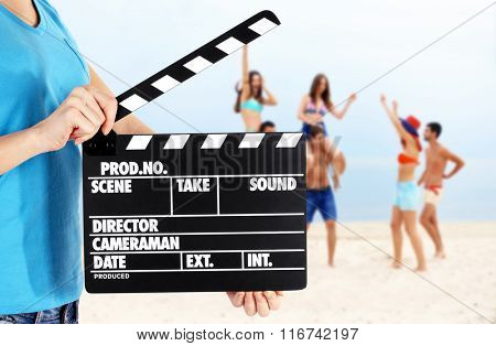 Operator holding clapperboard during the production of film outdoor