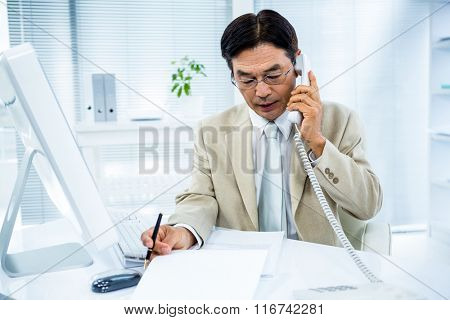 Serious businessman talking on the phone in his desk