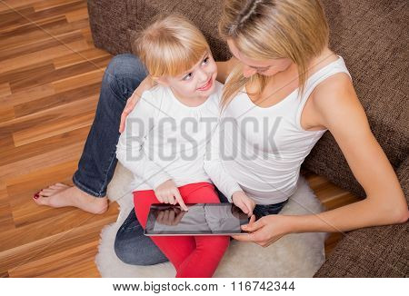 Little girl sitting in mother lap and pointing at tablet