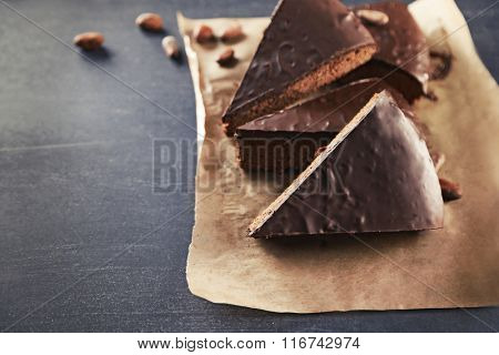 Pieces of frosting chocolate cake on parchment paper
