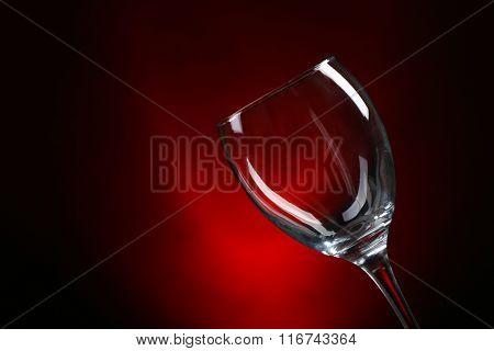 Empty wineglass on dark red background