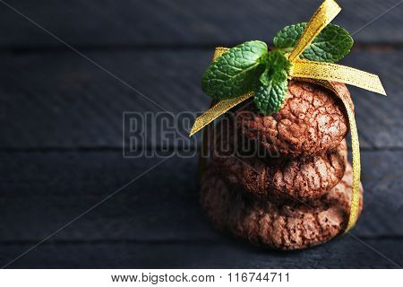 Chocolate chip cookie with yellow stripe and mint on wooden background