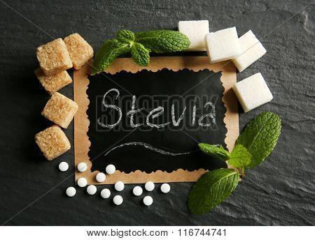 Word STEVIA in sugar frame on black background, close up