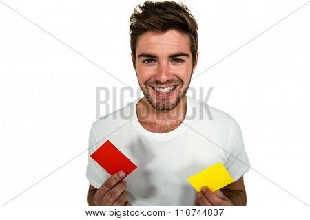 Handsome supporter holding red and yellow cards on white screen