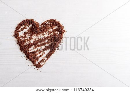 Chocolate Chips Arranged Into A Heart Shape Against Wooden Background