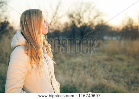 Smiling young woman on outdoors sunny background copy space