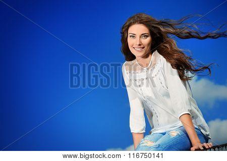 Carefree happy summer girl over blue sky background.