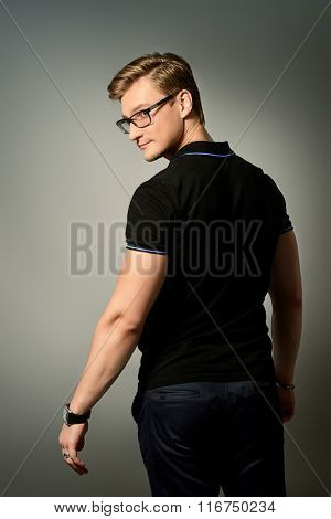 Attractive masculine young man in black clothes posing at studio over grey background. Men's beauty.