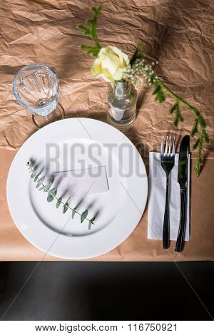 Decorated table ready for dinner. Beautifully decorated table set with flowers, candles, plates and