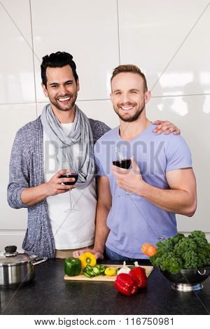 Smiling gay couple with red wine in the kitchen