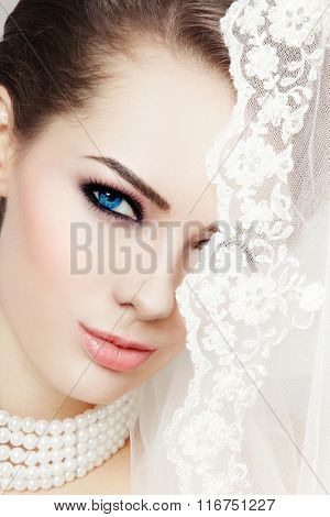 Close-up portrait of young beautiful bride with stylish make-up and bridal veil
