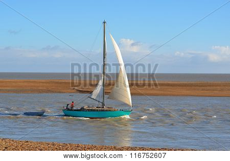 Yacht leaving Felixstowe Ferry at the mouth of the river Deben.