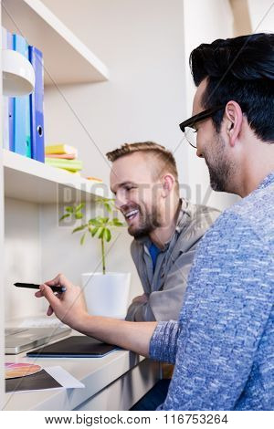 Happy gay couple using laptop in office