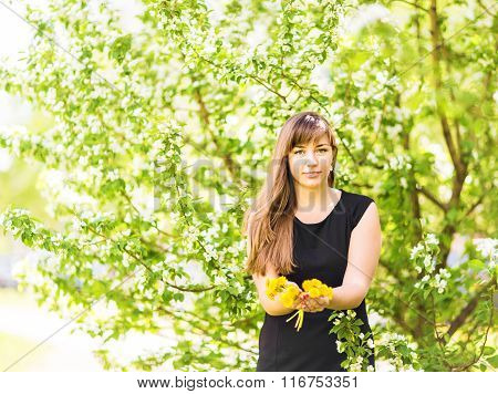 Portrait of beautiful girl with bouquet of yellow dandelions outdoor in spring, focus on eyes, apple