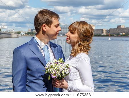 Handsome Groom And Beautiful Bride On The River Embankment