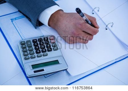 Close up view of desk with hands writing in a office