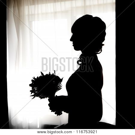 Black Silhouette Of Beautiful Bride With Posy Against White Window