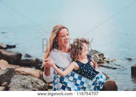 happy mother and daughter wrapped in quilt blanket spending time together on the beach on summer vac