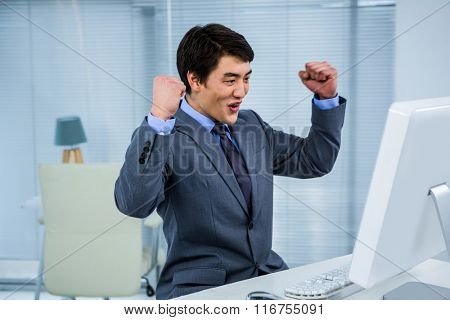 Businessman,celebrating with arms up in his office