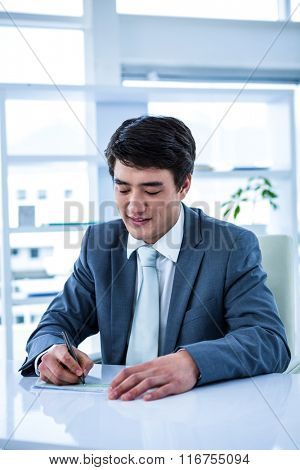 Smiling asian businessman completing a cheque in his office