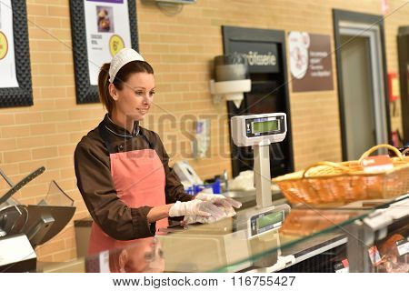 Woman pork butcher serving customer