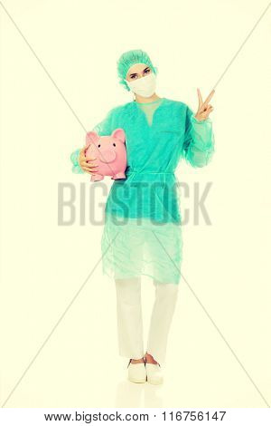 Female surgeon doctor with piggy bank shows victory sign