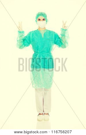 Smiling surgeonn doctor woman gesturing victory